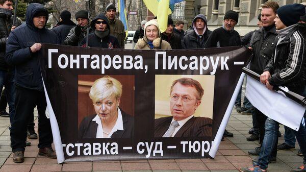 Участники акции протеста у Нацбанка Украины в Киеве, на плакате справа бывший первый замглавы Национального банка Александр Писарук