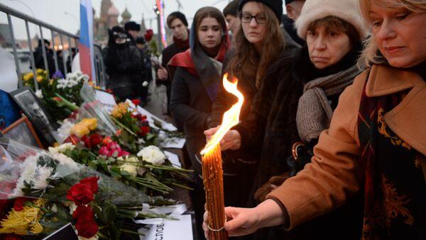 Женщины ставят свечи на месте убийства политика Бориса Немцова
