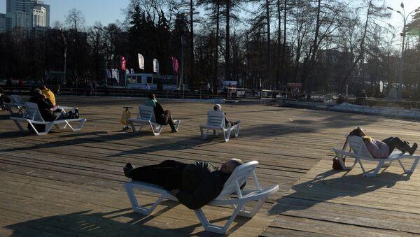 Жители Москвы отдыхают на солнце в парке Сокольники в Москве. Архивное фото
