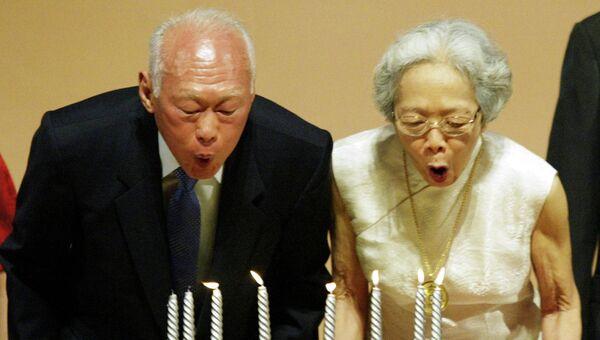 Бывший премьер-министр Сингапура Ли Куан Ю с супругой задувают свечи на праздновании 80-летия