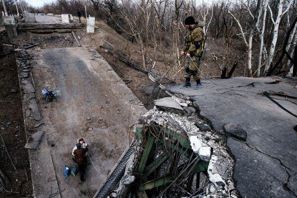 Ополченцы помогают житилям пересечь поврежденный мост в ЛНР