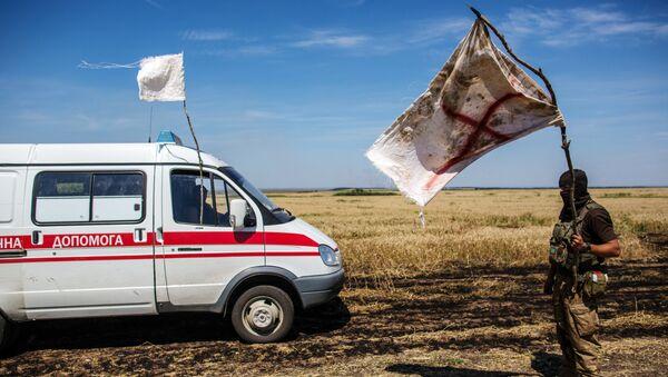 Украинский военный с белым флагом во время передачи убитых на нейтральной территории вблизи поселка Диброво возле российско-украинской границы в Донецкой области, 29 июля 2014