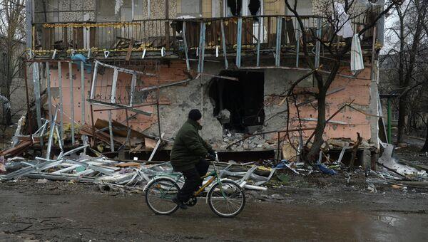 Житель города Дебальцево едет на велосипеде мимо разрушенного в результате обстрелов во время боевых действий жилого дома. Архивное фото