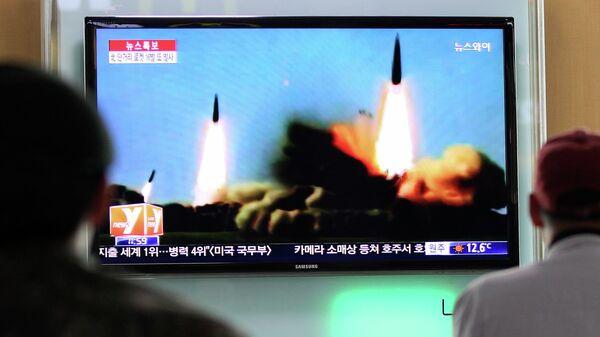 Люди наблюдают за запуском ракет Северной Кореей, архивное фото
