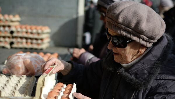 Пенсионерка покупает яйца на городской продовольственной ярмарке в Новосибирске