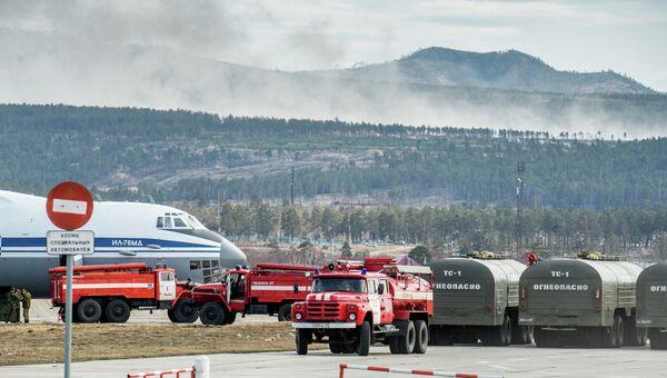 Пожарные автомашины и самолет ИЛ-76 МД во время подготовки к тушению лесных пожаров в Бурятии. Архивное фото
