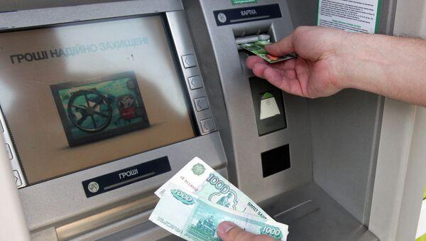 Житель снимает наличные денеги через банкомат. Архивное фото