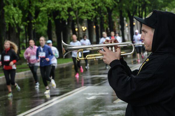 Музыкант играет на трубе во время благотворительного забега Бегущие сердца