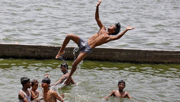 Мальчики спасаются от жары в реке Сабармати. Ахмедабаде, Индия, май 2015