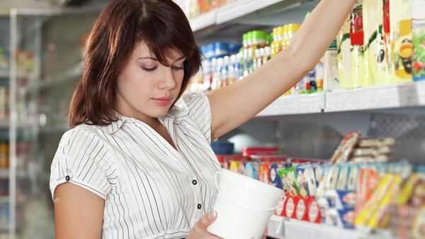 Девушка выбирает майонез в магазине