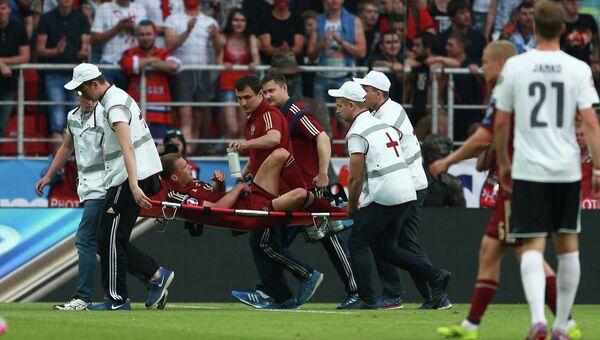 Игрок сборной России Василий Березуцкий покидает поле на носилках в матче против сборной Австрии