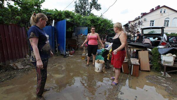 Местные жители во дворе дома, пострадавшего от подтопления после ливневых дождей в городе Сочи. Архивное фото