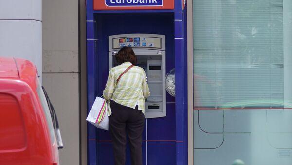 Местная жительница у банкомата в Афинах