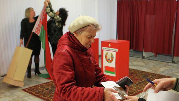Женщина получает бюллетень для голосования на выборах на одном из избирательных участков в Минске, Республика Беларусь. Архив
