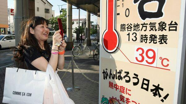 Женщина фотографирует термометр на улице в Кумагая, Япония