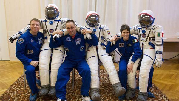 Члены основного экипажа 42/43-й длительной экспедиции на МКС Терри Вертс, Антон Шкаплеров и Саманта Кристофоретти во время примерки скафандров. Архивное фото