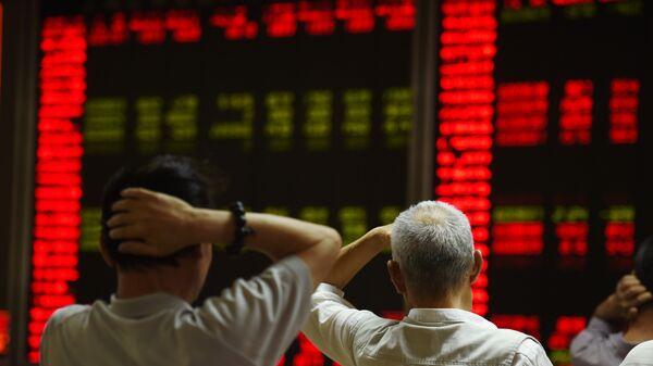 Инвесторы следят за котировками фондового рынка Китая в Пекине. Архив