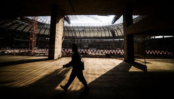 Рабочий идет по строительной площадке Большой Спортивной Арены Лужники в Москве