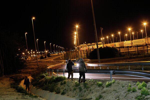 Мигранты идут вдоль дороги недалеко от Евротуннеля