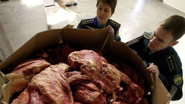 Работники таможенного поста досматривают груз задержанного мяса. Архивное фото