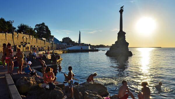 Отдыхающие и местные жители купаются у памятника затопленным кораблям на закате недалеко от Приморского бульвара в Севастополе. Архив