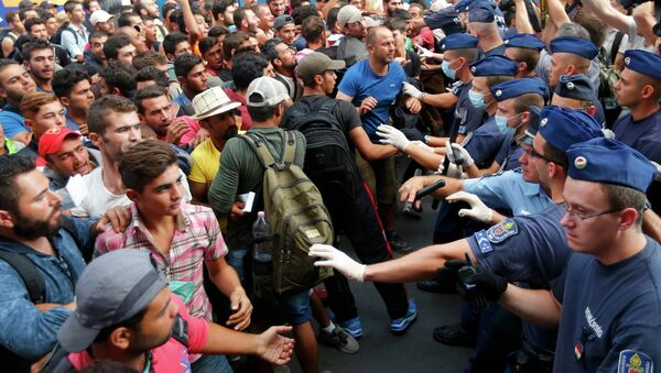 Венгерские полицейские сдерживают беженцев на железнодорожном вокзале Будапешта, Венгрия. 1 сентября 2015