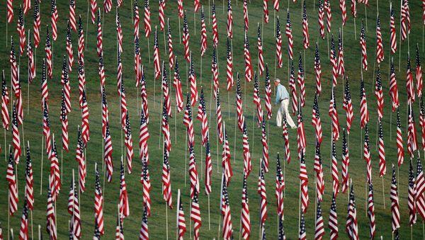 Мужчина идет среди флагов, выставленных по случаю 10-й годовщины с момента теракта 11 сентября 2001 года в Нью-Йорке