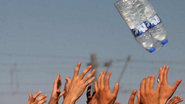 Мигранты ловят бутылки с водой на севере Греции недалеко от границы с Македонией