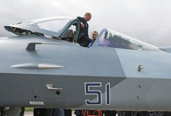 Председатель правительства России Владимир Путин с летчиком-испытателем (слева направо) у истребителя пятого поколения Т-50 разработки компании Сухой