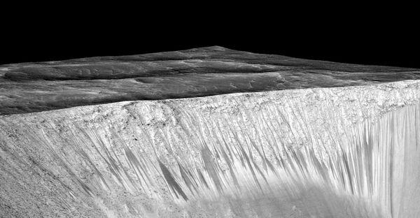Темные полосы, потенциальные марсианские соленые ручьи, на склонах кратера Гархи