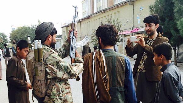 Боевики движения Талибан фотографируются на улице города Кундуз, Афганистан