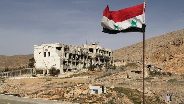 Сирийский флаг на фоне разрушенного дома в сирийском городе Маалюля в 55 км от Дамаска, который дважды захватывали и грабили боевики из группировки Джабхат ан-Нусра