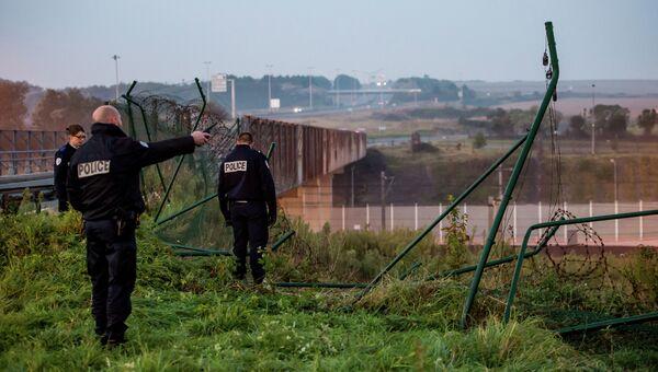 Полицейские у поврежденной ограды туннеля под Ла-Маншем в Кале. Архивное фото