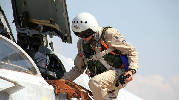 Российский летчик садится в самолет Су-24 перед вылетом с аэродрома Хмеймим