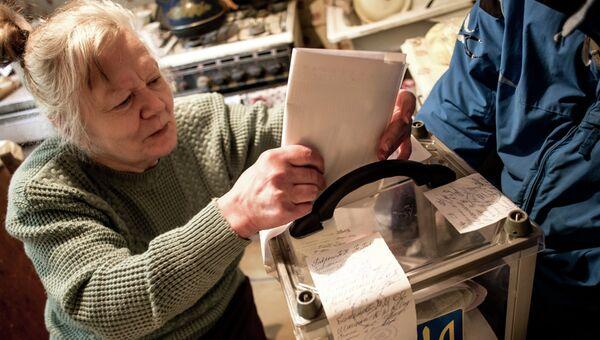 Пожилая женщина голосует на дому в Харькове во время выборов в органы местного самоуправления