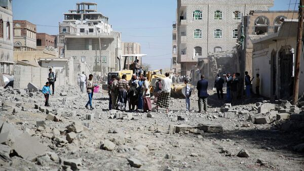 Люди на улице в столице Йемена Сане после нанесенного силами арабской коалиции авиаудара