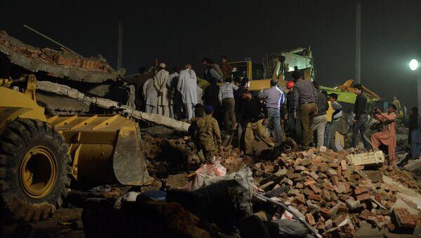 Пакистанские спасатели на месте разрушенного завода на окраине Лахора