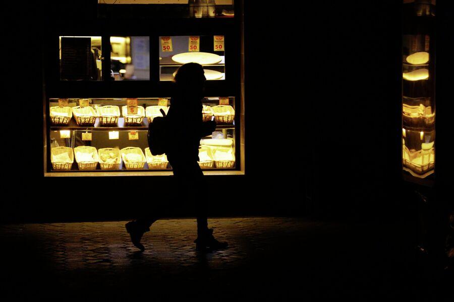 Прохожий возле кофейни во время отключения электроэнергии в Симферополе