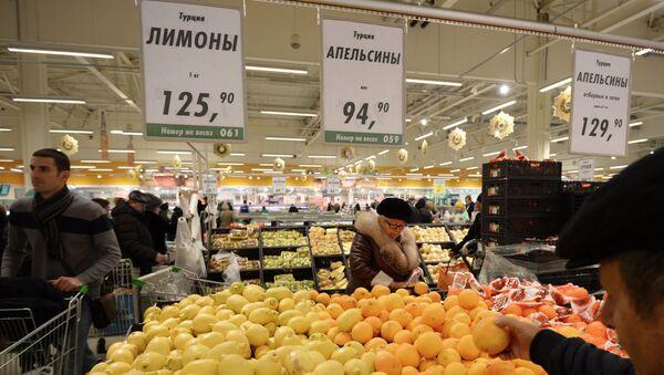 Покупатели у прилавка с лимонами и апельсинами из Турции в торговом зале гипермаркета Глобус