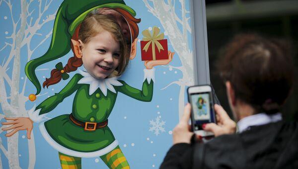 Девочка фотографируется в канун Рождества в Нью-Йорке