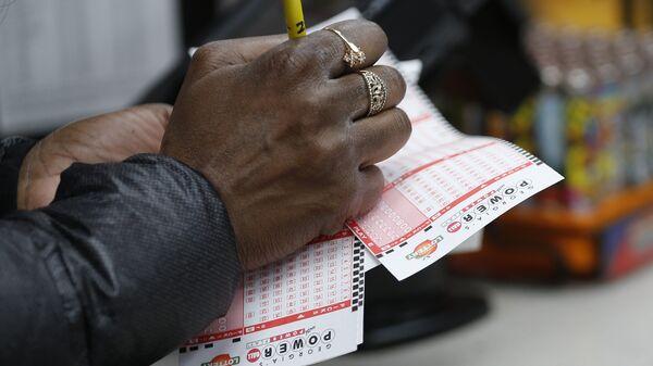 Мужчина проверяет лотерейные билеты Powerball максимальный выигрыш которой на данный момент составляет 1,5 миллиарда долларов
