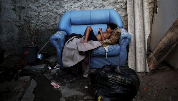 Ребенок лежит на диване возле своего дома в Бразилии
