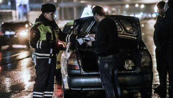 Сотрудник дорожно-патрульной службы проверяет документы у водителя во время проведения оперативно-профилактического мероприятия Невод на улице Верхние поля в Москве