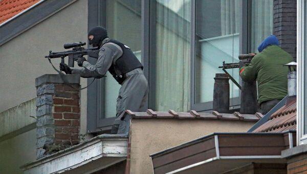Сотрудники служб безопасности месте перестрелки спецназа с подозреваемыми террористами неподалеку от Брюсселя. 15 марта 2016