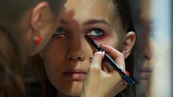 Визажист наносит макияж перед началом показа дизайнера KSENIASERAYA в рамках Mercedes-Benz Fashion Week Russia в ЦВЗ Манеж