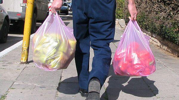 Мужчина с полиэтиленовыми пакетами на улице в Петах-Тикве, Израиль