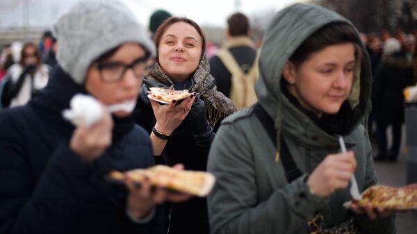 Девушки едят блины во время масленичных гуляний в Парке Горького в Москве
