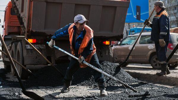Рабочий разравнивает асфальт во время ремонта дорожного покрытия на улице Кирова в Омске