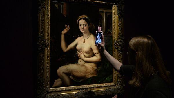 Посетительница фотографирует картину Джулио Романо Дама за туалетом, или Форнарина. Архивное фото