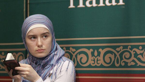 Молодая мусульманка читает Коран. Архивное фото